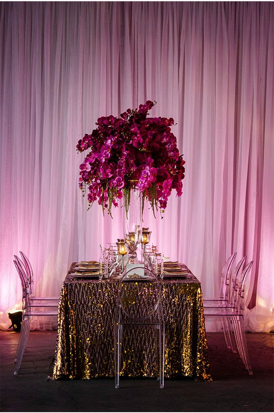 a bold radiant orchid wedding floral arrangement and centerpiece paired with gold decor around for a refined look