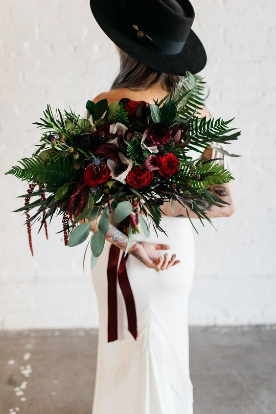 a bold wedding bouquet of burgundy and red blooms, greenery and ferbs, thistles and burgundy ribbons