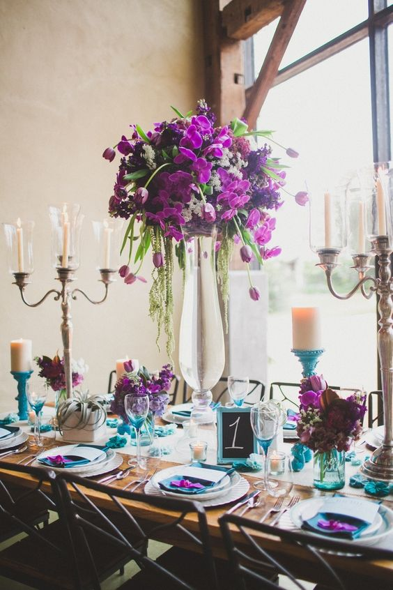 a bold wedding centerpiece with deep purple and radiant orchid blooms and greenery plus bold florals on the table