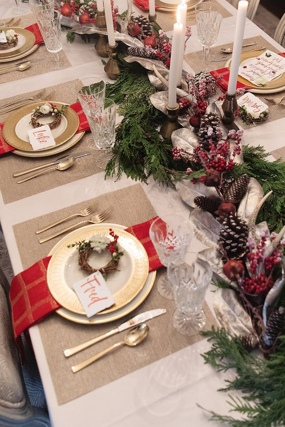 a bold winter or Christmas wedding tablescape with berries, pinecones, candles, fit, red candles, mini wreaths and gold cutlery