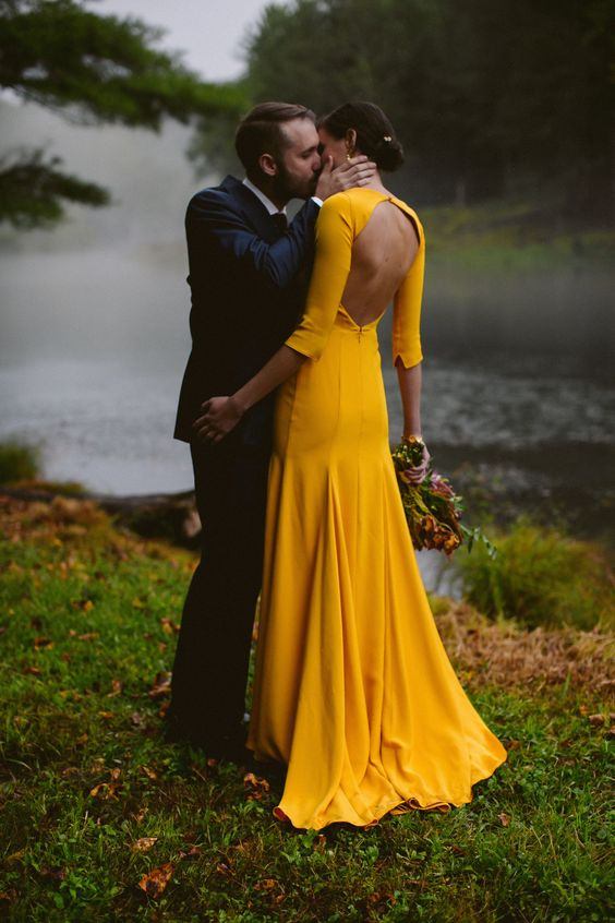 a bold yellow mermaid wedding dress with long sleeves and a cutout back is a modern and very bold idea for summer or fall bride
