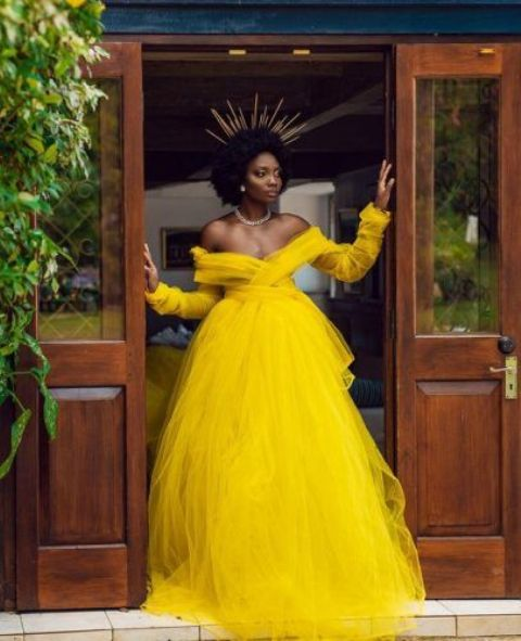 a bold yellow off the shoulder wedding ballgown with long sleeves and a layered full skirt plus a crown for a royal look