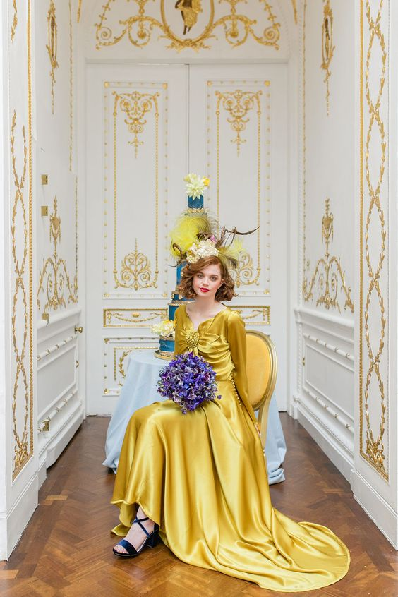 a bold yellow silk A-line wedding dress with a large flower on the bodice and long sleeves for a bold statement