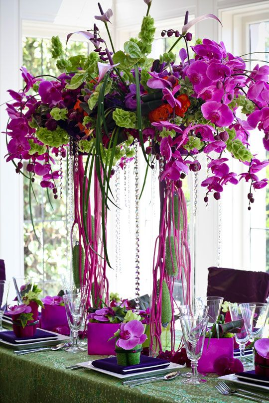 a bright tall wedding arrangement of radiant orchid florals and greenery and crystals plus radiant orchid boxes and blooms