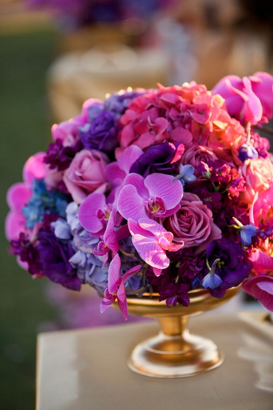 a bright wedding centerpiece of a gold bowl with deep purple, hot pink and radiant orchid blooms