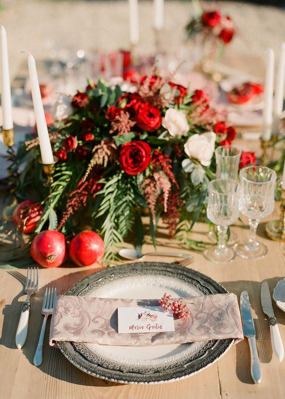 a bright wedding tablescape with pomegranates, greenery, white and red blooms and berries on the place setting