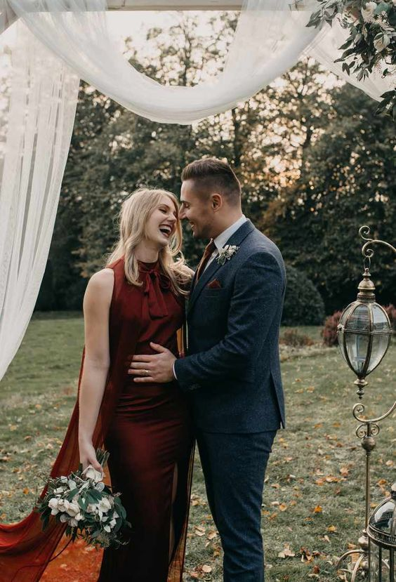 a burgundy halter neckline sheath wedding dress with a bow and a cape is a gorgeous idea to rock