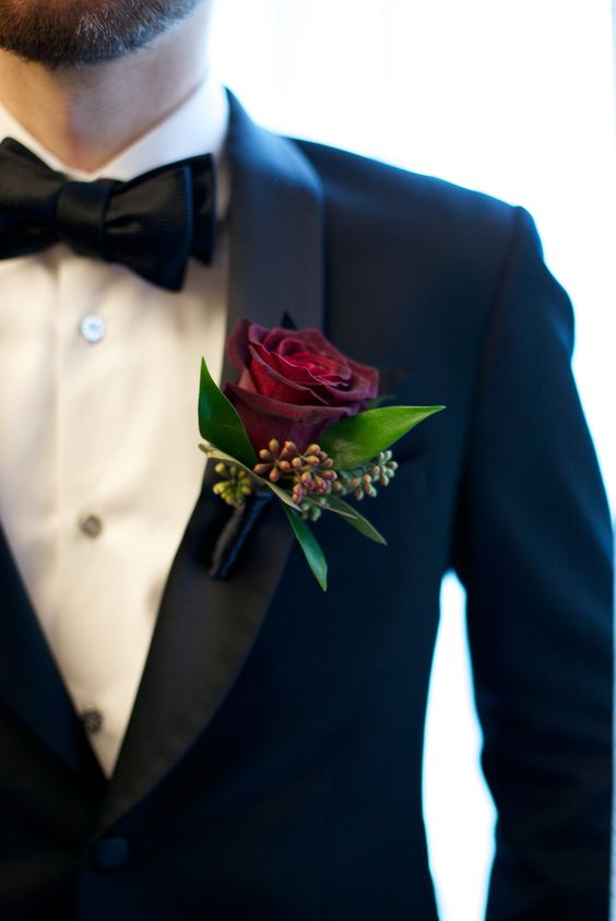 a burgundy rose boutonniere with leaves and berries is a bold touch to a classic black tux look
