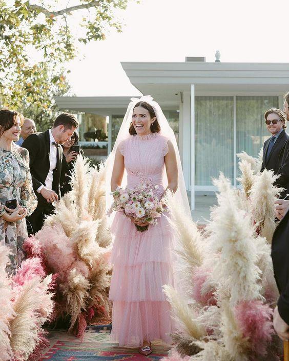 a chic light pink A-line wedding dress with a draped bodice, a high neckline, no sleeves and a tiered skirt is romantic