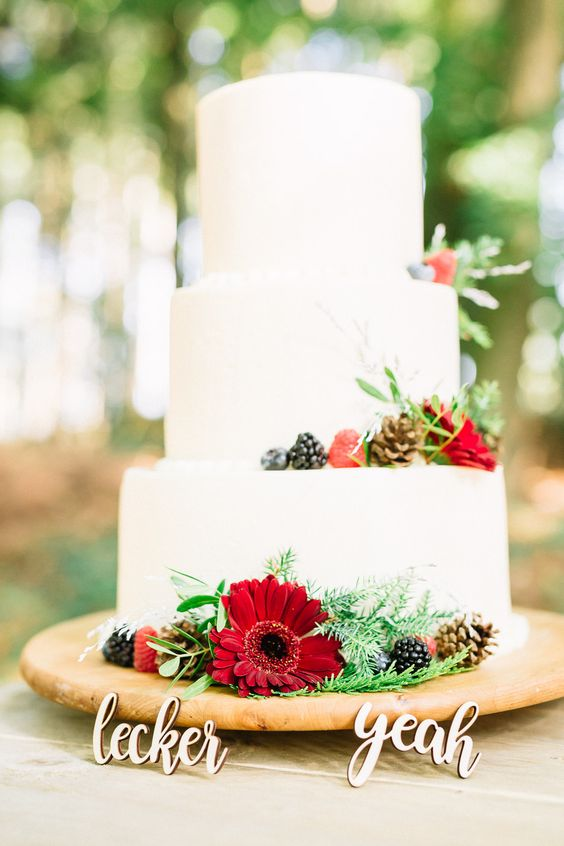 a chic white wedding cake with pinecones, fir, blooms, berries, greenery and fun calligraphy toppers