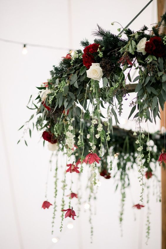 a chic winter wedding chandelier of greenery, white and burgundy blooms, berries and fir for a winter wedding