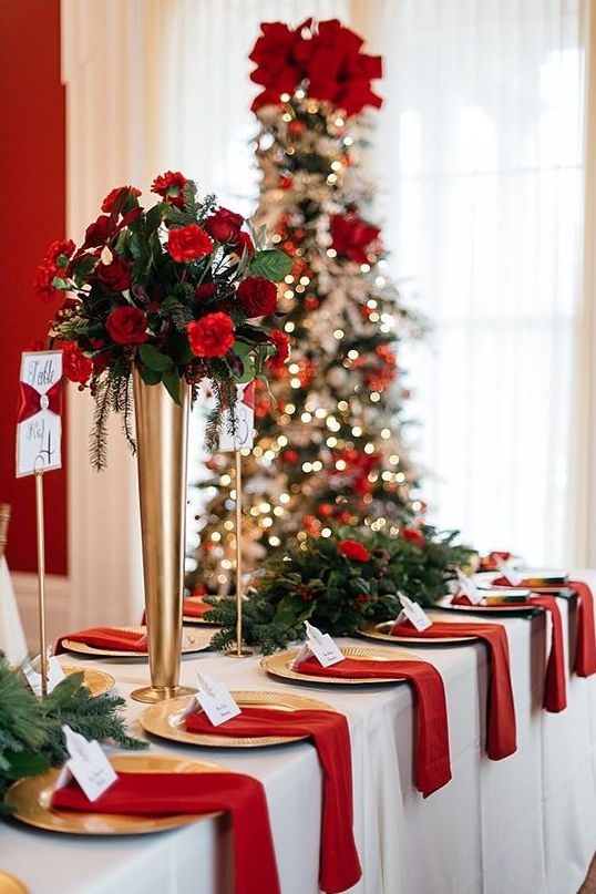 a classic Christmas wedding tablescape with greenery, fir and red and burgundy blooms and red napkins