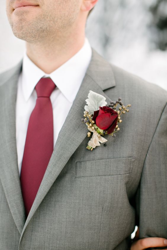a classic winter wedding boutonniere with berries, usual and gilded ones, a pale leaf and a burgundy rose plus a matching tie