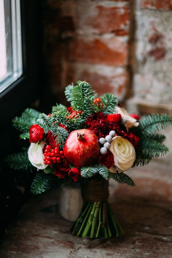 a cozy winter wedding bouquet of fir, red and white blooms, berries and pomegranates for a winter or Christmas wedding