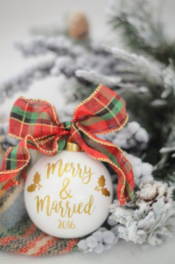 a cute white and gold Christmas ornament with a plaid bow is a gorgeous Christmas wedding favor option to rock