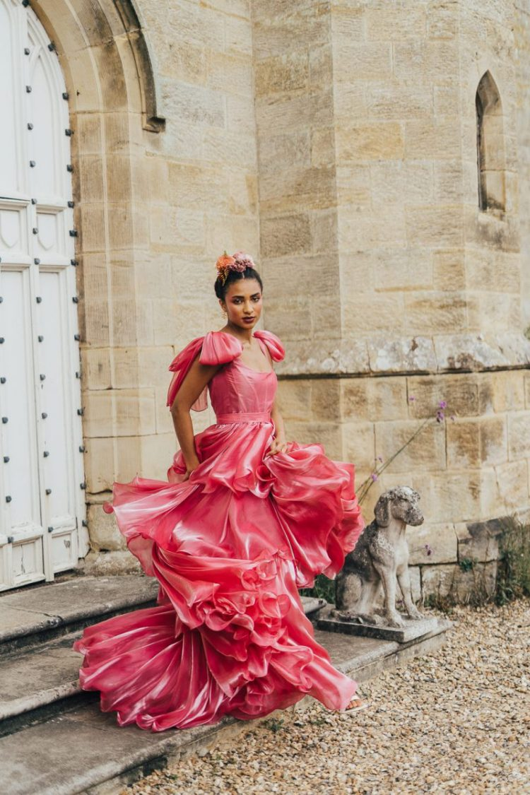 a fabulous pink satin wedding dress with a layered skirt and bow sleeves for a playful bride