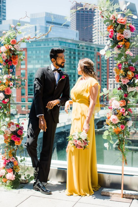 a flowy yellow wedding dress with a draped ruffle bodice for a flower-filled and bright wedding