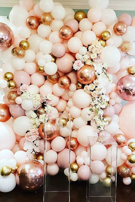 a fun wedding backdrop made of blush, pink, gold and rose gold balloons, neutral and pastel blooms is a bold idea