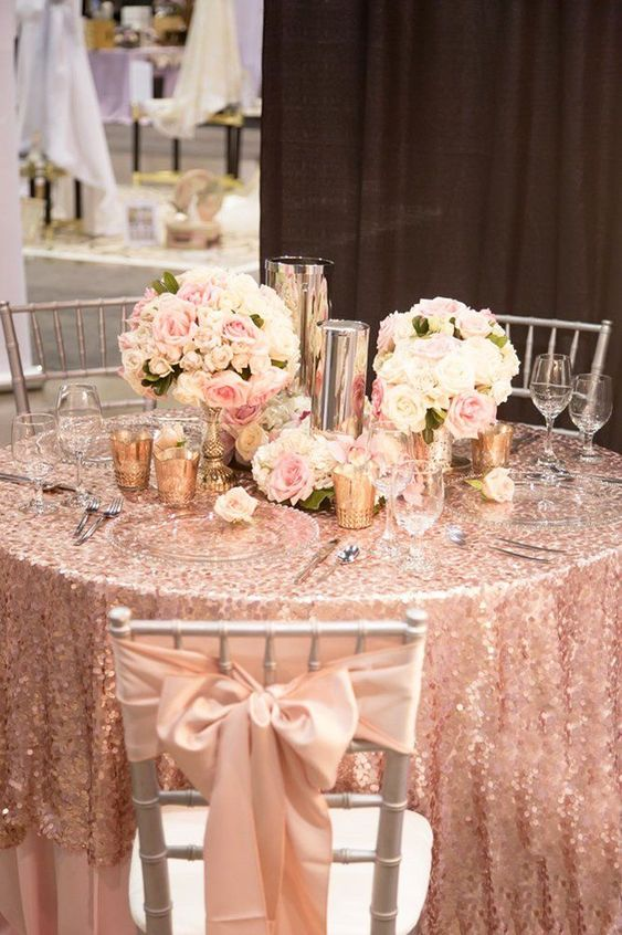 a glam rose gold sequin tablecloth, rose bows on the chairs and touches of godl and silver for a glam tablescape