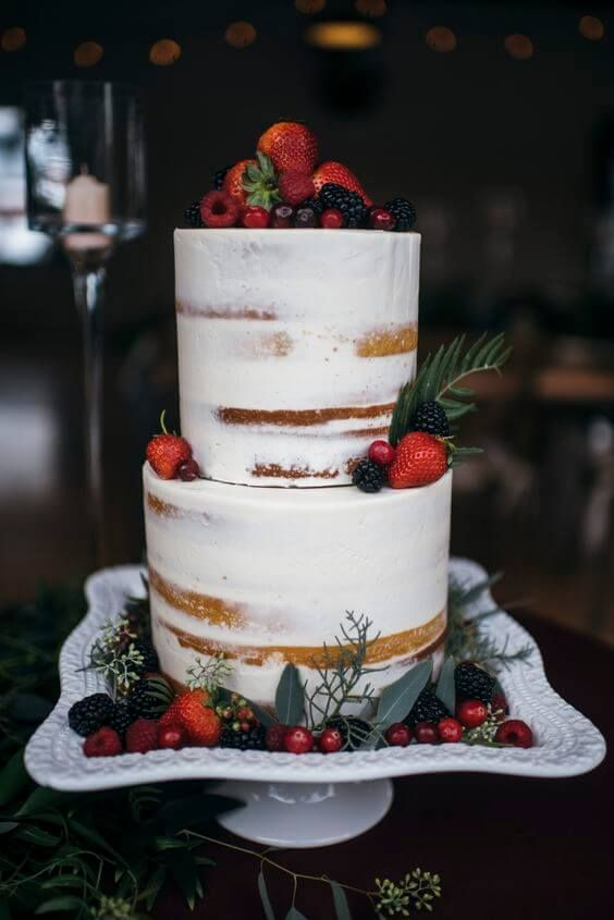 a gorgeous naked wedding cake with strawberries, blackberries, raspberries, greenery for a winter wedding