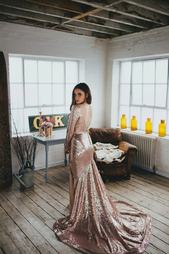 a gorgeous rose gold mermaid wedding dress with an open back and a train, with long sleeves and a high neckline