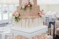 a large square wedding cake with rose gold dots and fresh blooms and greenery is a beautiful option