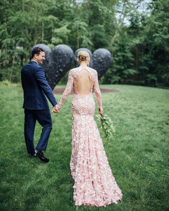 a light pink wedding dress with a cutout back, long sleeves fully covered with floral petals is a lovely and pretty idea