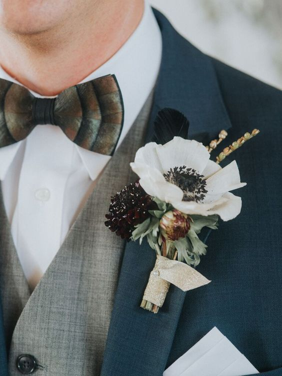 a lush wedding boutonniere with a white and deep purple bloom, greenery and a feather for a vintage look