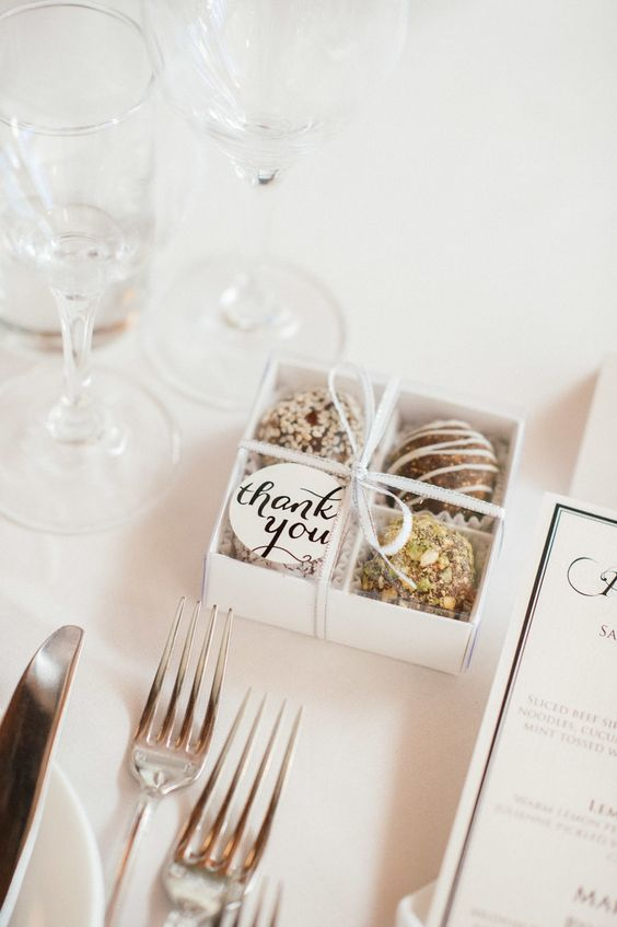 a mini box with various chocolate and a tag on top is a lovely wedding favor idea to enjoy