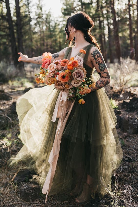 a moody green A-line wedding dress with a layered skirt and thick straps plus peep toe booties for a woodland bride