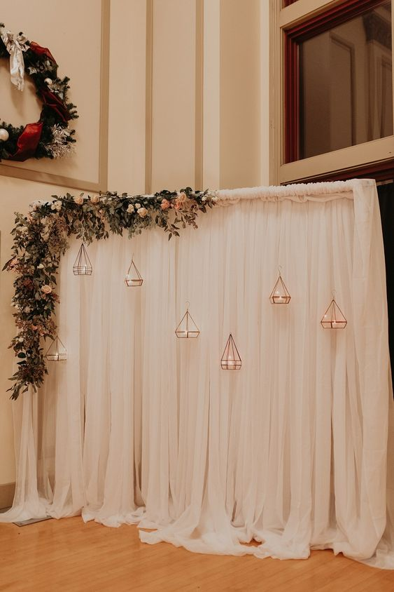 a neutral curtain backdrop with greenery, pastel blooms and rose gold candle lanterns is very romantic and beautiful