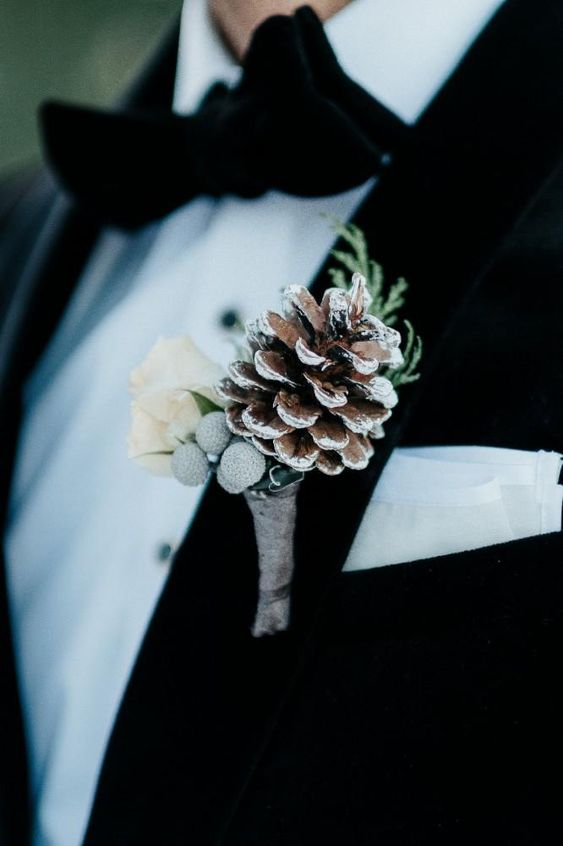 a neutral wedding boutonniere of berries, a snowy pinecones, white blooms and greenery