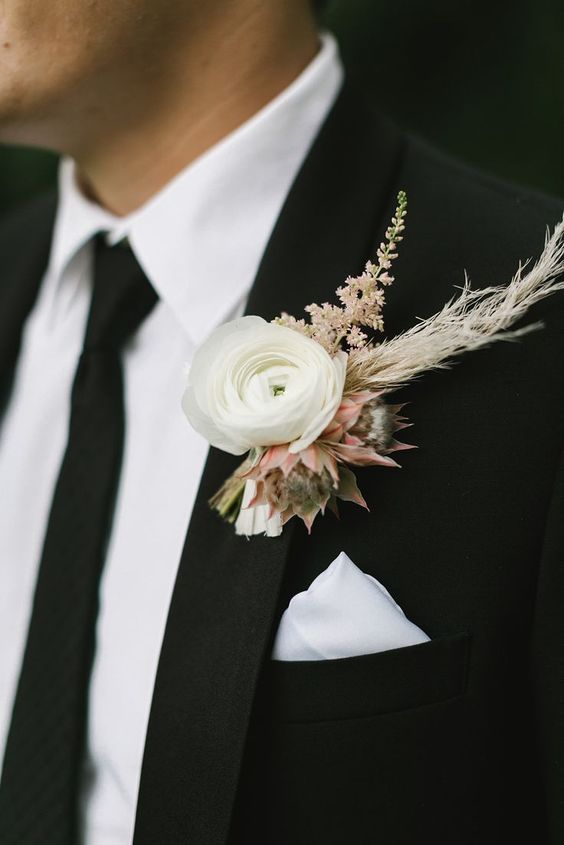 a neutral winter wedding boutonniere of a white bloom and pink ones, dried herbs and blush blooms