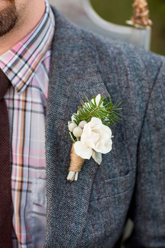 a neutral winter wedding boutonniere of white blooms, neutral berries, fir and twine wrapping