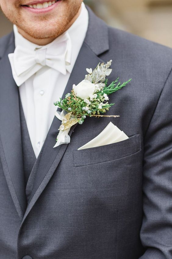 a neutral winter wedding boutonniere with berries, greenery and white blooms, sticks and a white ribbon