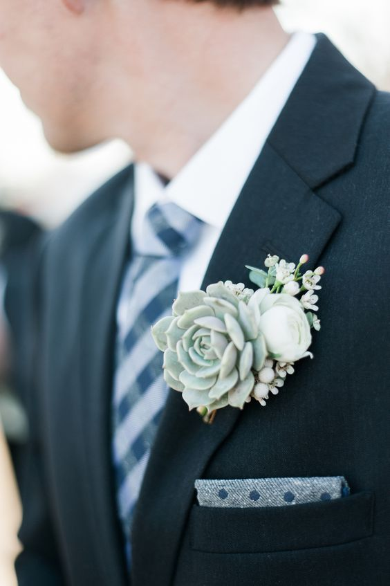 a pale winter wedding boutonniere of a succulents, white blooms and berries is a pretty accessory to rock