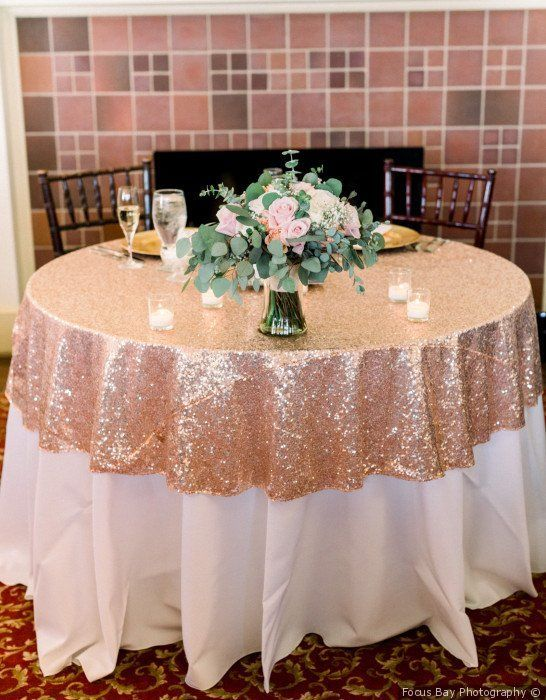 a partly rose gold sequin tablecloth paired with a lvoely pink rose centerpeice and candles is wow