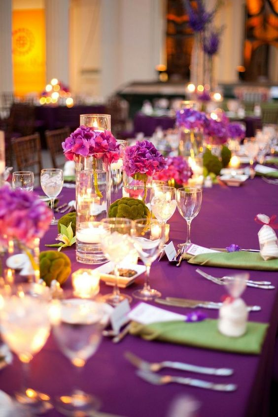 a radiant orchid wedding tablescape with bold blooms, moss balls and green napkins plus candles