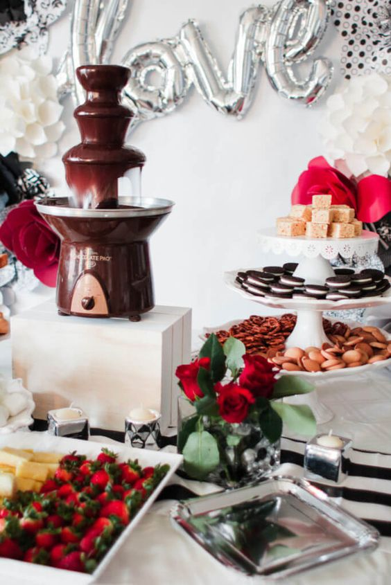 a refined and glam wedding chocolate bar with a fountain, bright blooms, lots of fruits, berries, cookies and other stuff