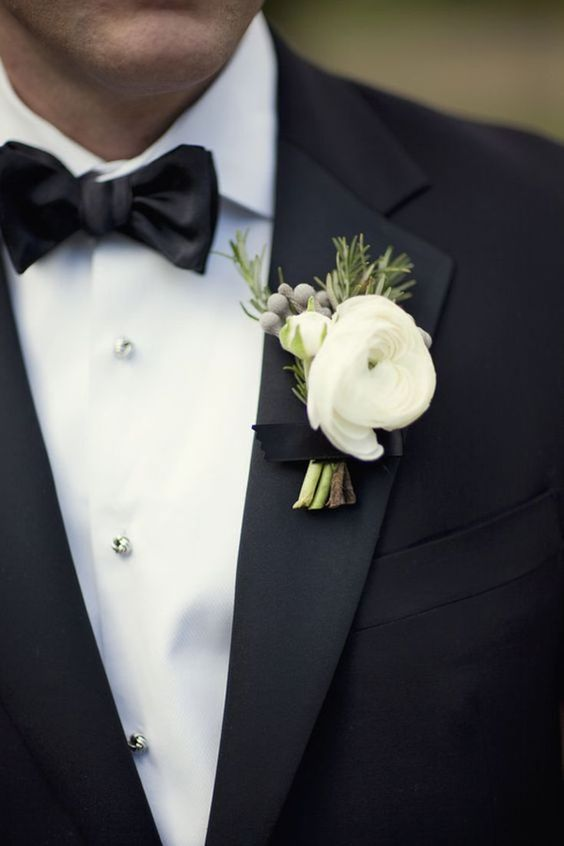 a refined neutral wedding boutonniere of white blooms, berries and greenery for accessorizing a tux