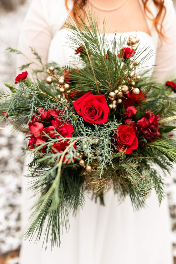 a romantic Christmas wedding bouquet of greenery and fir, gilded berries, red and burgundy blooms