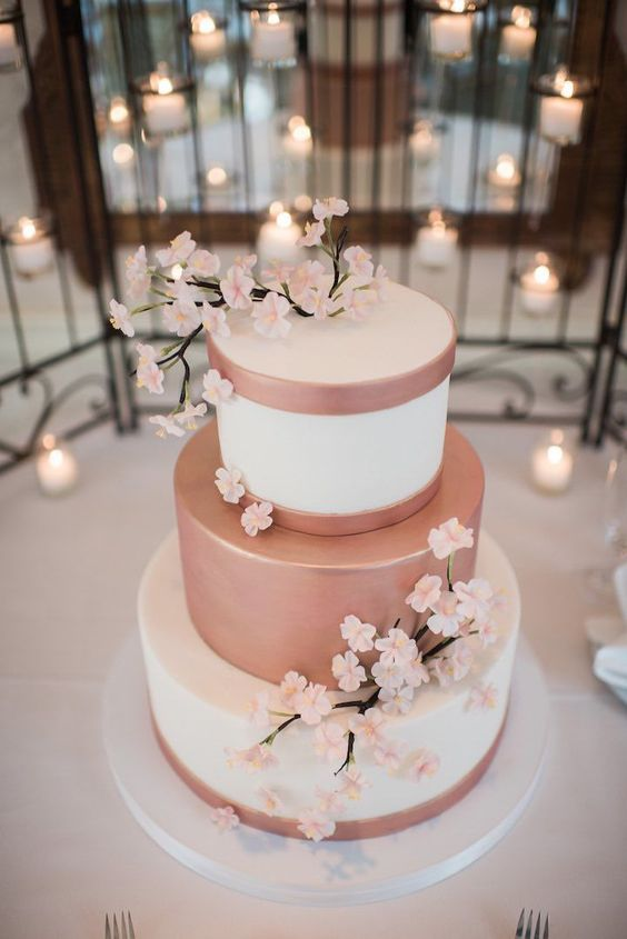 a romantic wedding cake in white and rose gold, with sugar sakura branches is a chic and cool idea