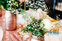 a rose gold sequin table runner and rose gold jars with white, pink blooms and baby's breath for a chic look