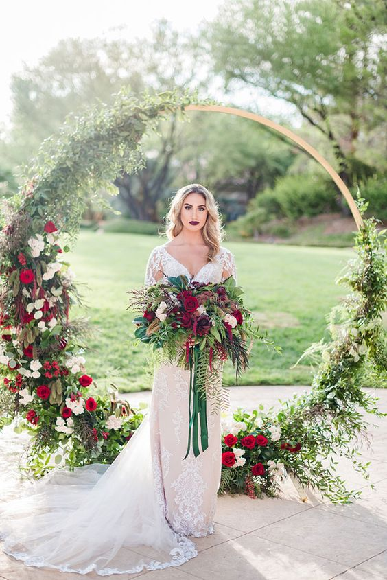 a round wedding arch covered with greenery, white and burgundy blooms and a matching wedding bouquet