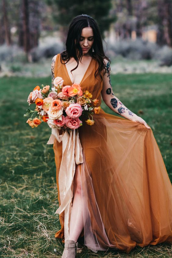 a rust-colored A-line wedding dress with a depe neckline, no sleeves, a front slit and nude peep toe booties for a fall bride
