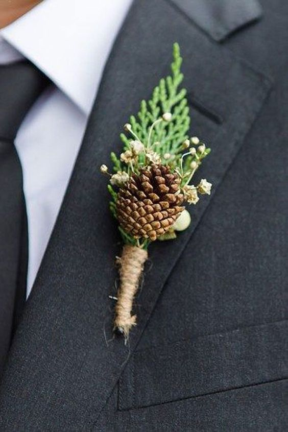 a rustic wedding boutonniere of a pinecone, berries, greenery and twine wrap for a cozy and comfy outfit