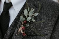 a rustic winter wedding boutonniere of berries, greenery and with a twine wrap for a boho look