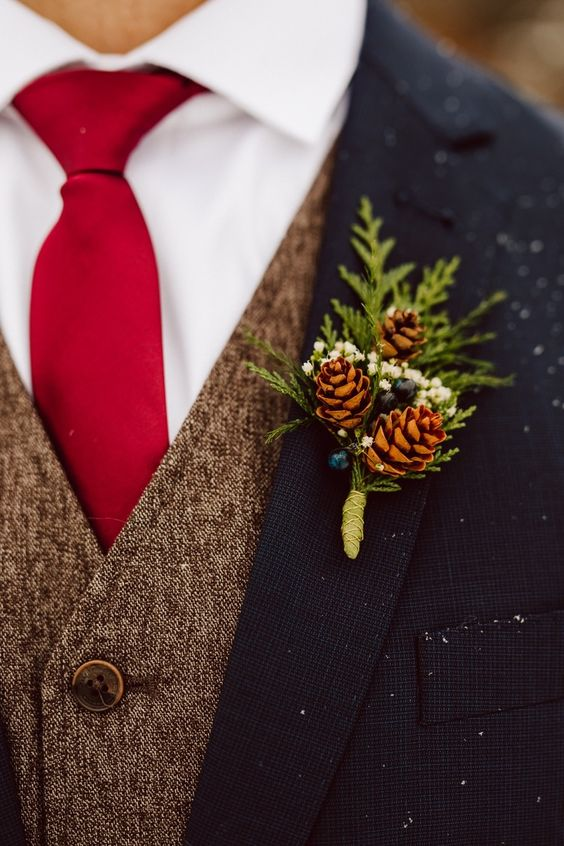 a rustic winter wedding boutonniere of pinecones, white blooms, greenery and berries for a cozy feel
