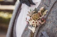 a rustic winter wedding buttonhole with white and blush blooms, berries, leaves and feathers for a boho feel