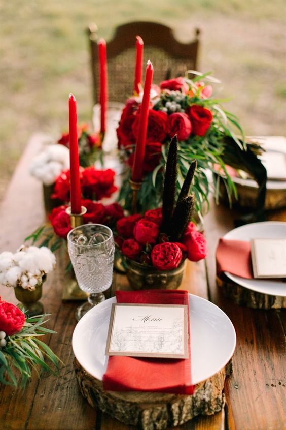 a rustic winter wedding tablescape with wood slices, red blooms, candles and napkins, greenery and cotton